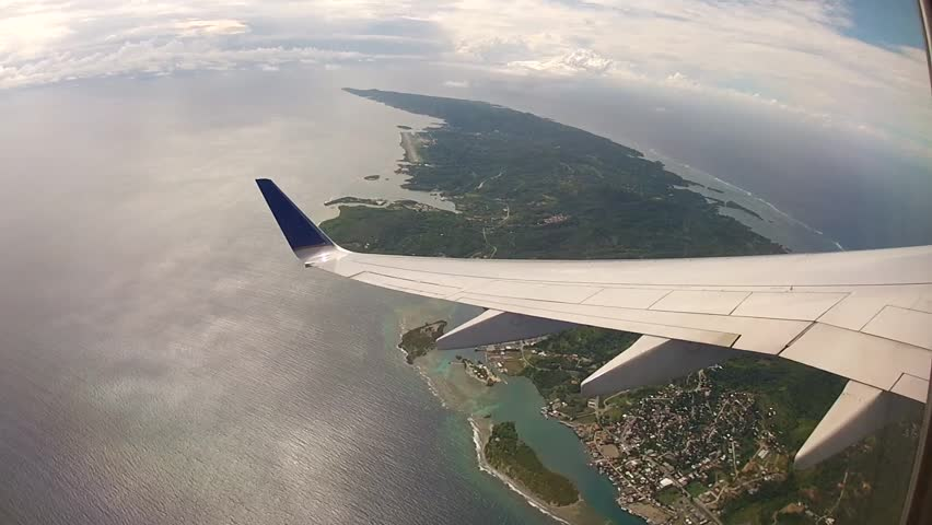Commercial jet turns left over NW Roatan Island, departing.