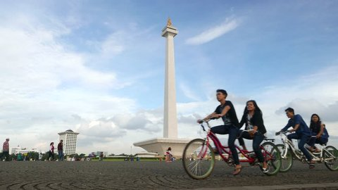 JAKARTA, INDONESIA - MARCH 08, 2015: Tandem bicycle ride against Monas, weekend evening time. People leisure on center of Jakarta, Merdeka Square. Tall National Monument tower rising against blue sky