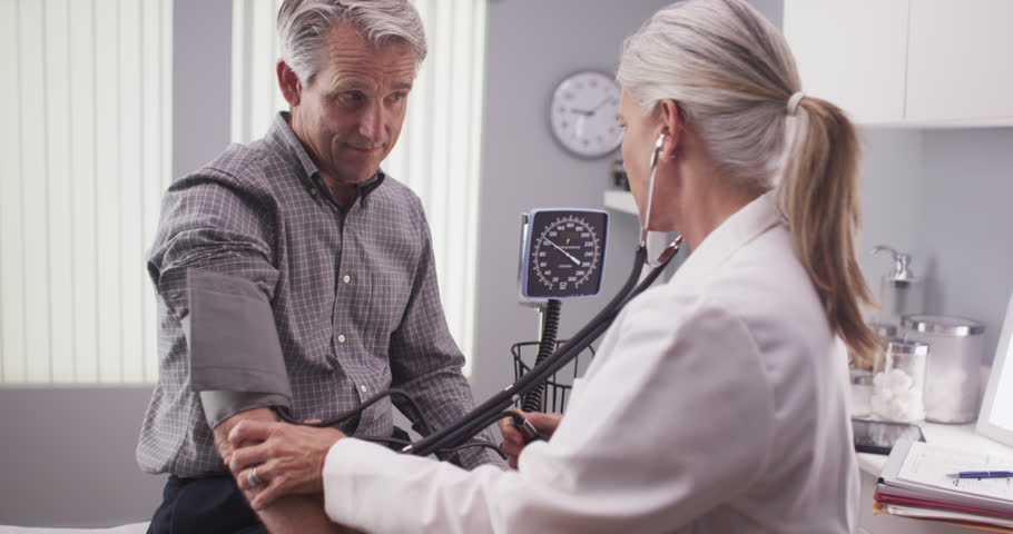 Middle-aged male patient having blood pressure checked