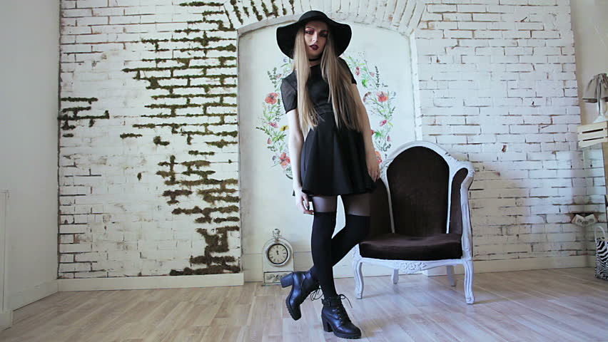 High fashion shot of blonde woman with straight hair in black hat and stylish dress posing on white brick wall background. Wearing silk collar, black stockings and ankle boots