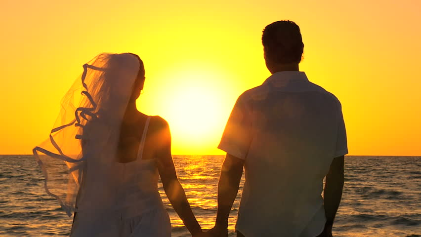 Bride & groom in silhouette at sunset on the beach after their wedding filmed at 60FPS