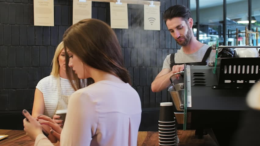 Friendly waitress behind the counters communicates with customers and settles payment on touch screen electronic tablet device | Shutterstock HD Video #13307657