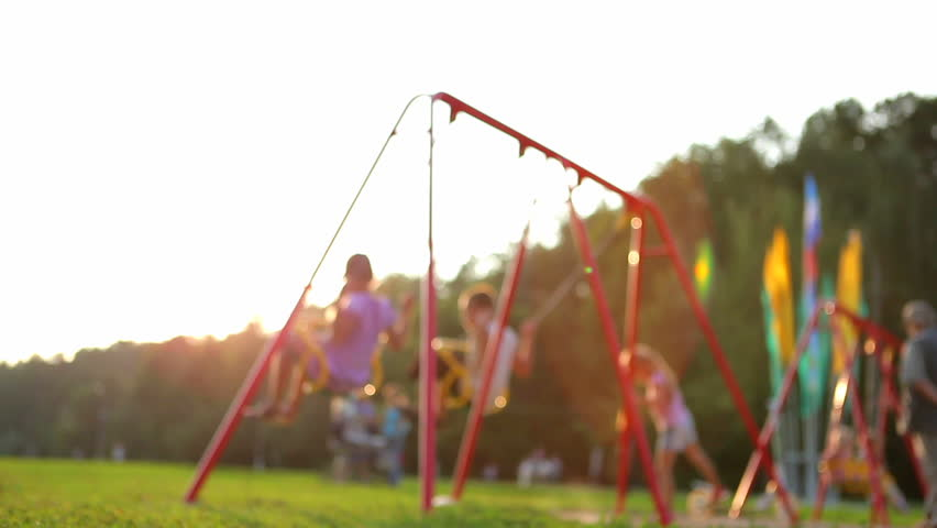 children ride on the swings at the playground. defocused