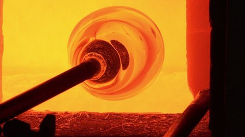 Glass-blower working in his workshop/the molten glass is picked with the blowing rod