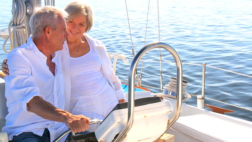 Healthy retired couple steering a course for the future aboard their luxury sailing boat filmed at 60FPS