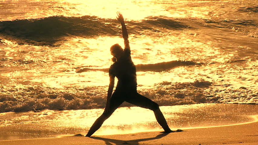 Slim athletic girl in silhouette practicing yoga on the beach at sunrise filmed at 60FPS