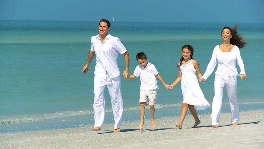 Happy young family having fun on vacation skipping outdoors on the beach filmed at 60FPS