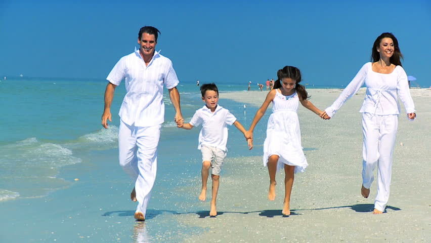 Attractive healthy young family having fun together on vacation on the beach filmed at 60FPS | Shutterstock HD Video #1333846