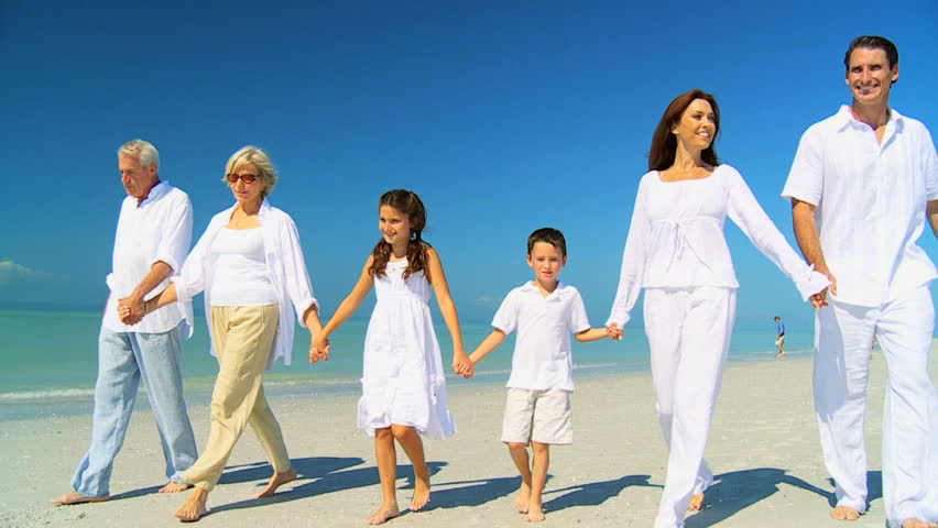 Three generations of a loving family happily walking together on the beach filmed at 60FPS