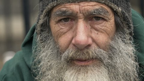 Homeless old man looking in the camera: poor man, beggar man, asking for charity