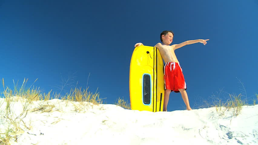 Young boy standing on a sand dune with his bodyboard filmed at 60FPS