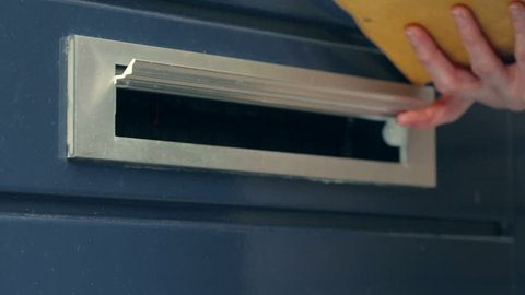 Paper mail being delivered through a door mounted mailbox opening.