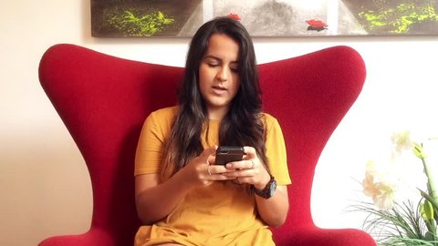 Young brazilian woman sitting in armchair typing on her smartphone.