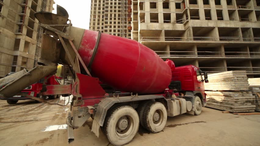 Concrete mixer stand at building place, truck full of sand arrives, workers work around