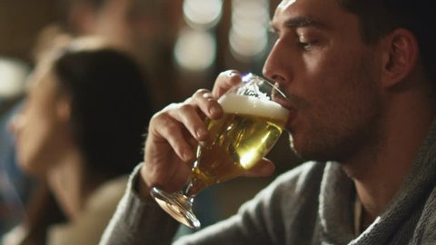 Attractive man is drinking lager beer that was given to him by bartender in a pub. Shot on RED Cinema Camera in 4K (UHD).
