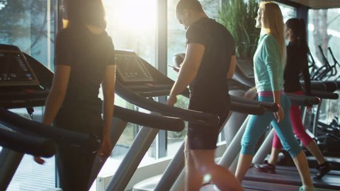 Young athletic man is using smartphone while exercising and running on treadmill in sport gym. Shot on RED Cinema Camera in 4K (UHD).