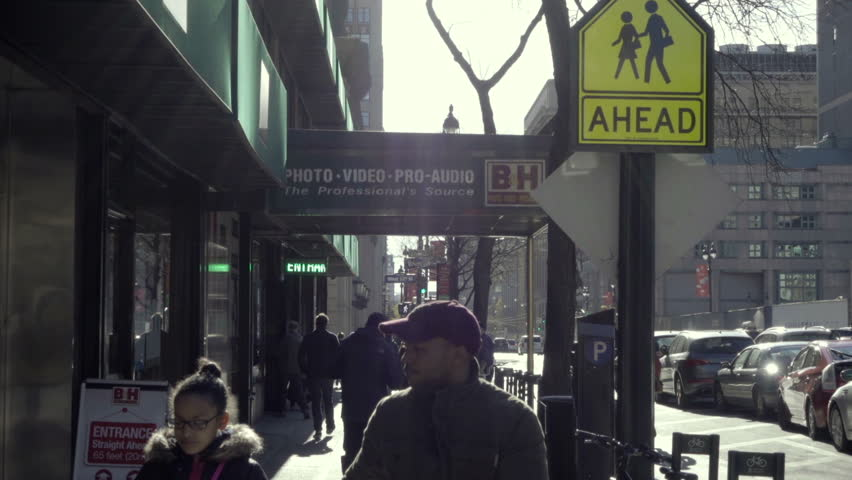 NEW YORK - NOV 29, 2015: young black male and girl walking outside BH Photo Superstore in Manhattan in the cold winter NYC. B&H Photo is a famous electronics store in NYC.