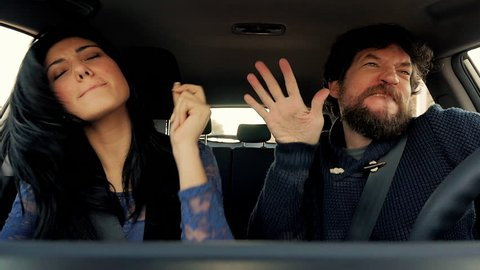 Funny man and woman dancing like crazy in car slow motion
