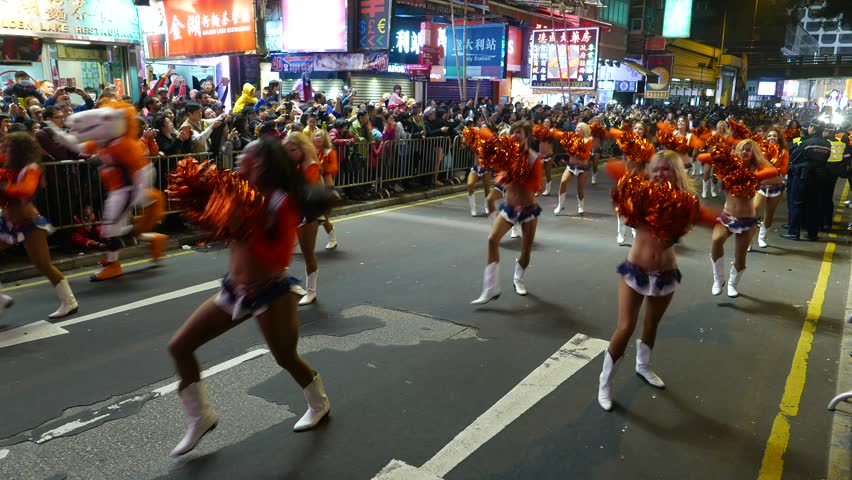 HONG KONG - FEBRUARY 19, 2015: Cheer-leading show on night festival procession, anniversary Chinese New Year celebration parade. Girls with puffs walk and dance on night street