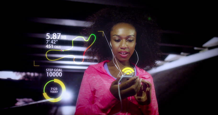 An attractive female runner using  fitness tracker and heart rate monitor app while jogging. Shot on RED Epic.