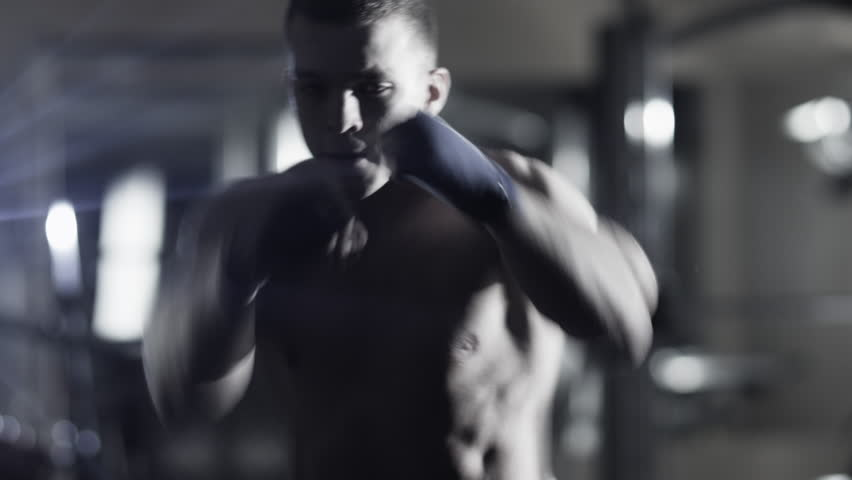 Professional male boxer is training punches and kicks in dark gym. Shot on RED Cinema Camera in 4K (UHD). | Shutterstock HD Video #13456517
