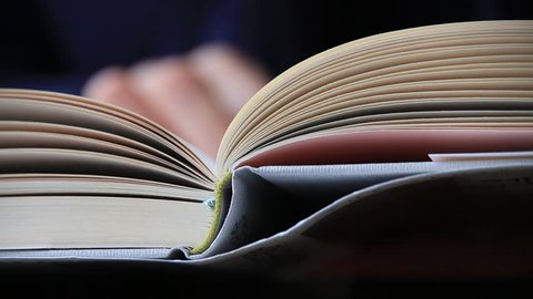 Close up shot of woman's hand reading a book indoors