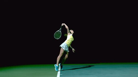 Female Tennis Player Serving in Slow Motion - Wide Shot of court with black background