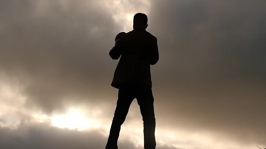 Silhouette of man in suit boxing against sun and clouds view