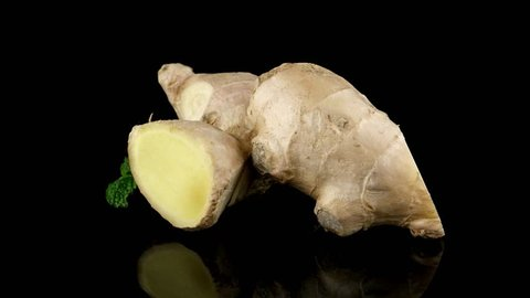 Ginger root on black reflective background.