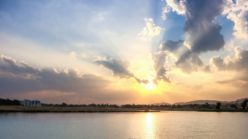 Beautiful sunset behind the lake with sunbeam and fluffy cloud - timelapse