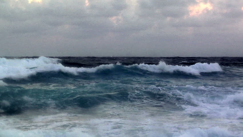 Moody, stormy waves crash into shore under a storm clouded sky.
