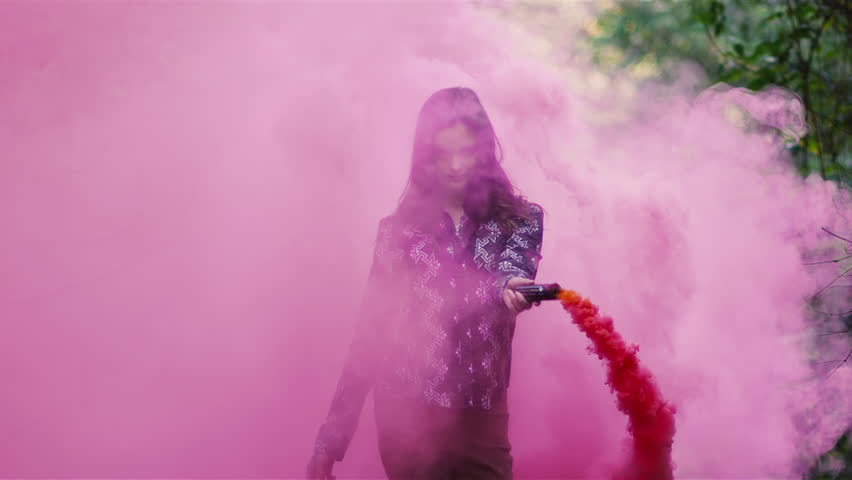 Beautiful girl in a forest waves around a pink smoke grenade and then tosses it behind her, slow motion