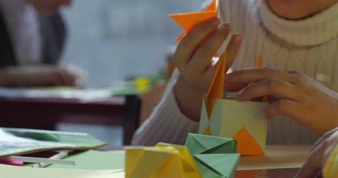 KIEV/UKRAINE - JUL 14 2015: Paper origami. Three kids make origami from colored paper. Origami contest. Making of kusudama. Assemble of modular origami, unit origami. Close view. Indoors. Kiev,