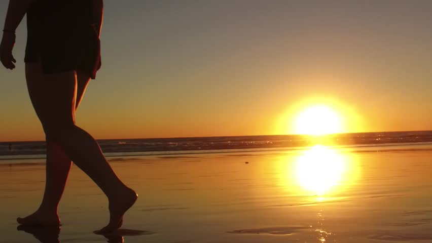 Medium shot tracking girl walking on beach at sunset with beautiful reflection on sand and sunburst in between her legs / Silhouette Girl Walking on Beach | Shutterstock HD Video #13667087