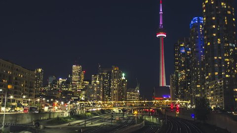 TORONTO, CANADA - CIRCA AUGUST 2015: Long-exposure night timelapse of the Toronto cityscape from the west facing the CN Tower and Rogers Centre, from the GO train station overpass.