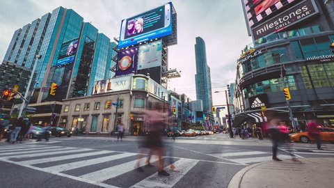 TORONTO, CANADA - CIRCA AUGUST 2015: Timelapse of downtown Toronto Yonge and Dundas Square, with billboards, shopping, tourism, & restaurants. Summer day with pedestrians and traffic in the streets.