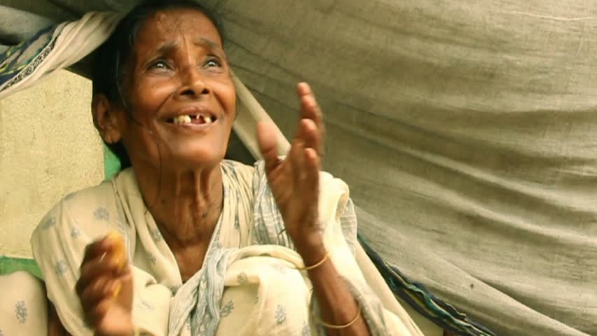 Elderly Indian woman smiles and fold hands in gratitude upon receiving some vegetarian food. She has been put out of home by a big flood