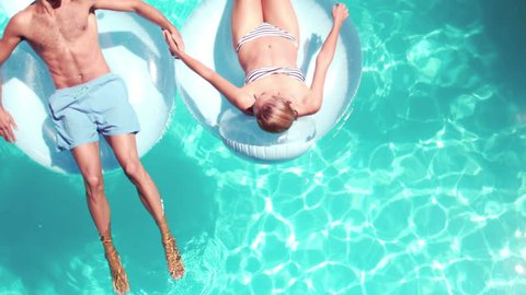 Attractive couple relaxing on lilos in pool in slow motion