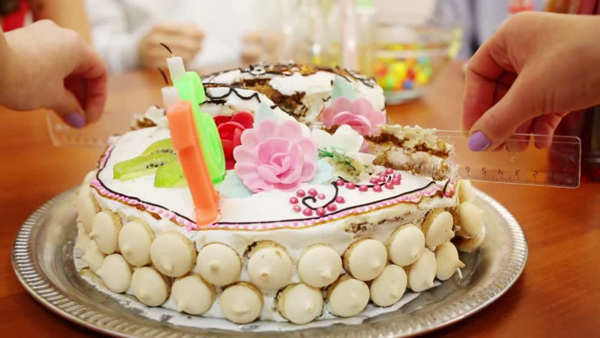 Hands Cut Birthday Cake By Ruler On Table During Holiday