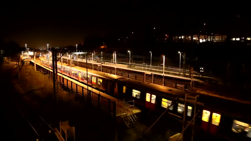 overground train passes at night in london with reflections of lights from windows on bank.