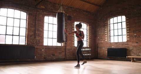 Beautiful Kickboxing woman training punching bag in fitness studio fierce strength fit body slow motion kickboxer series