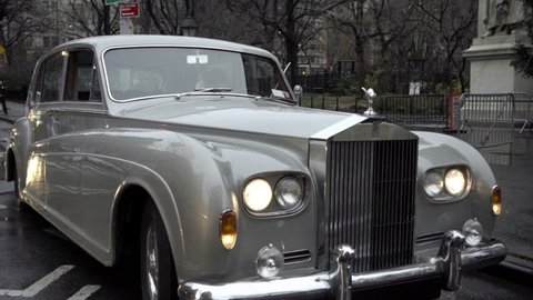 NEW YORK - DEC 20, 2015: Rolls-Royce classic luxury car panning to Lower Fifth Avenue traffic, cars and taxi cabs at crosswalk 1080p HD NYC. 5th Ave is a major thoroughfare that runs north and south.