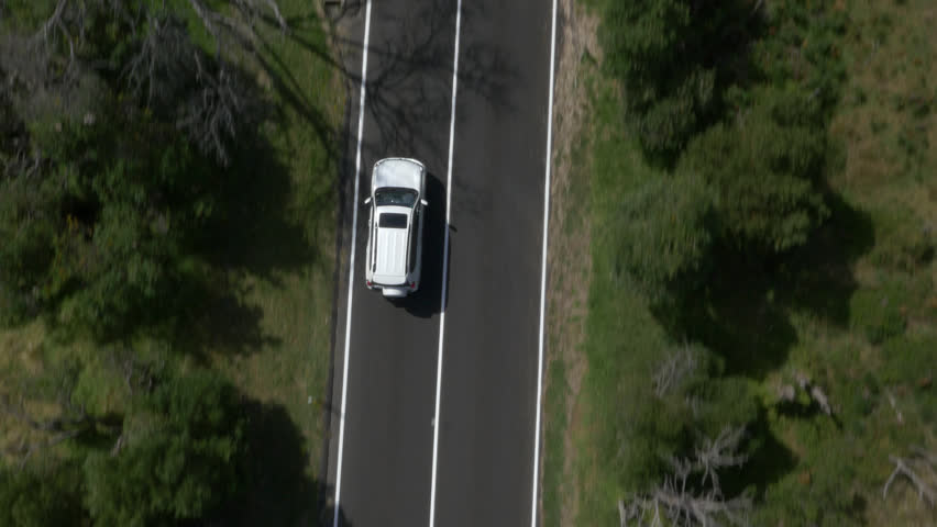 Aerial shot of a car driving along a road through the forest | Shutterstock HD Video #13792667