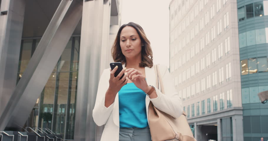 Beautiful mixed race business woman walking through city connected using smart phone