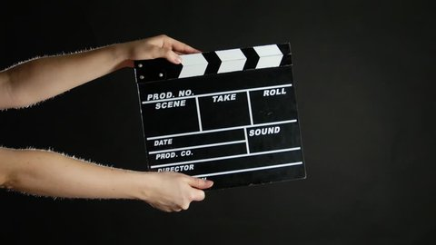 Hands with movie production clapper board, on black