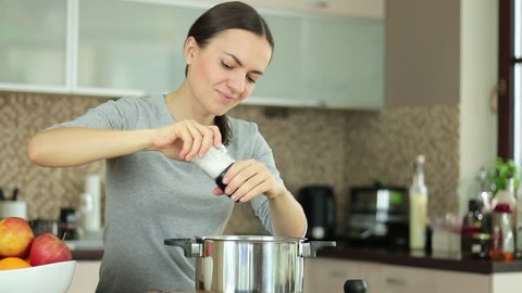 Woman with a pepper mill cooking and testing the food in the kitchen