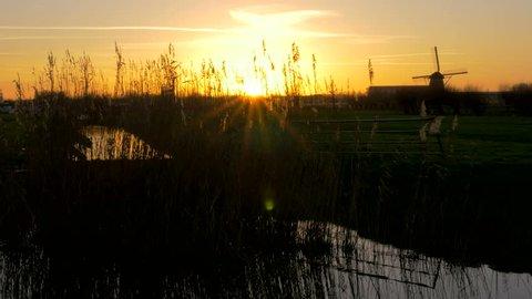 Beautiful Sunset shot of a Dutch Windmill in the polder at Kinderdijk the Netherlands - 4K Ultra HD