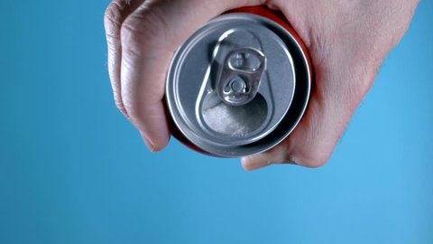 hand holding cola refresh drink pouring out a massive amount of white sugar content in calories diet and nutrition and unhealthy sugar abuse concept isolated on blue background