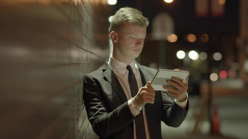 Young caucasian businessman using tablet computer browsing the internet outdoors in the city at night. portrait shot of entrepreneur brainstorming ideas | Shutterstock HD Video #13926536