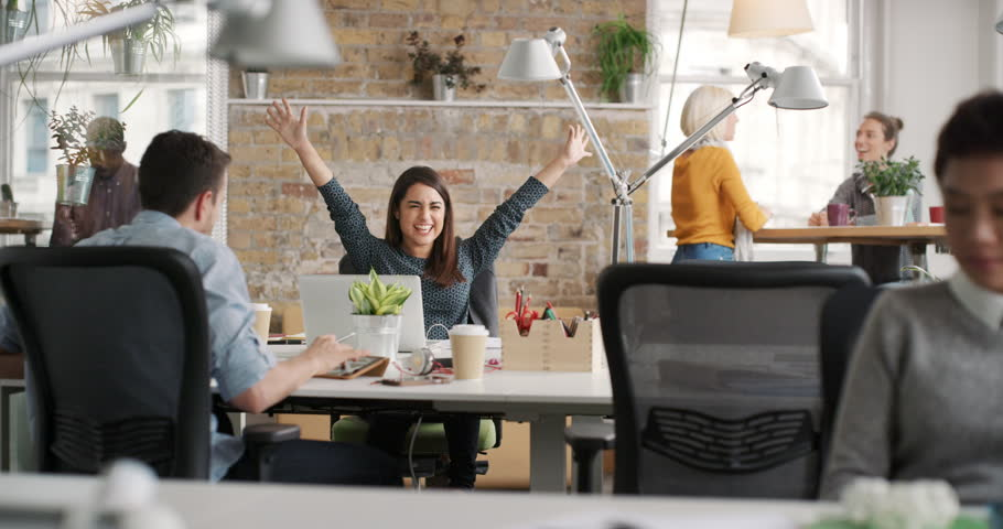 Business woman with arms raised celebrating success watching sport victory on laptop diverse people group clapping expressing excitement in office | Shutterstock HD Video #13947467